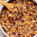 Wild rice stuffing with butternut squash, apples, cranberries, pecans and pepitas in a metal skillet with a wooden spoon in it.