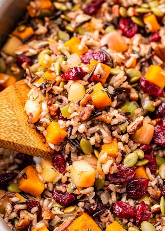 Closeup photo of Wild rice stuffing with butternut squash, apples, cranberries, pecans and pepitas. A wooden spoon is scooping some up.