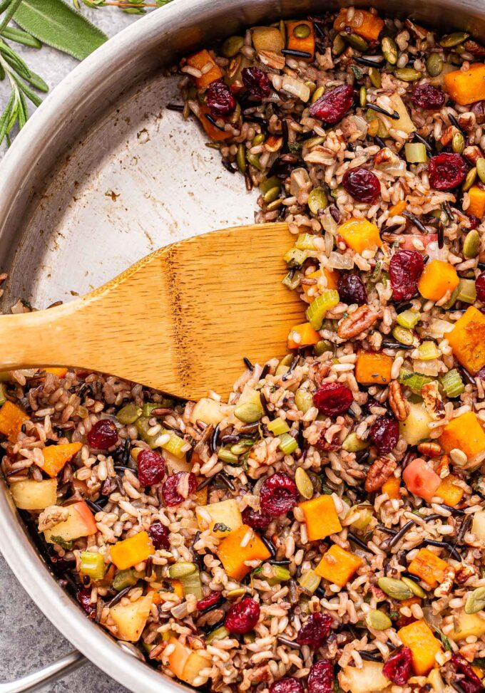 Wild rice stuffing with butternut squash, apples, cranberries, pecans and pepitas in a metal skillet with a wooden spoon in it. A serving of the stuffing is missing from the skillet.