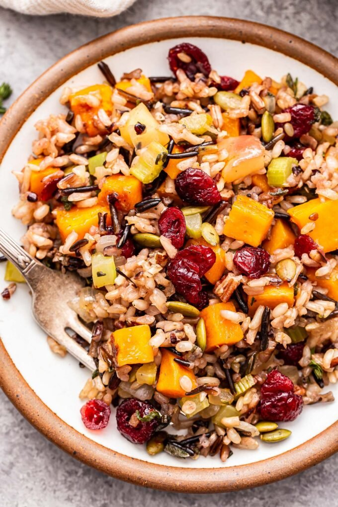 Wild rice stuffing with butternut squash, apples, cranberries, pecans and pepitas on a white plate with a fork.