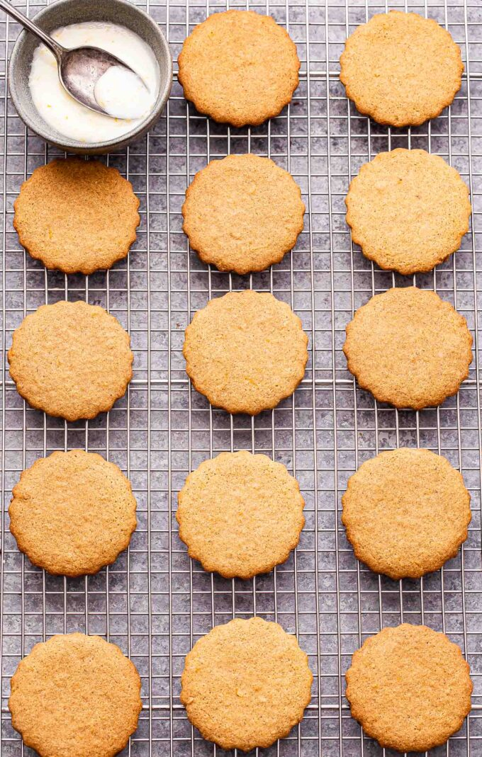 chai ginger cookies, unglazed on a wire cooling rack with a bowl of glaze.