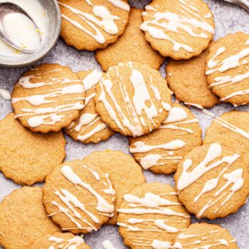 chai ginger cookies drizzled with white glaze scattered on a countertop. A spoon of chai spice next to them and bowl of the glaze.