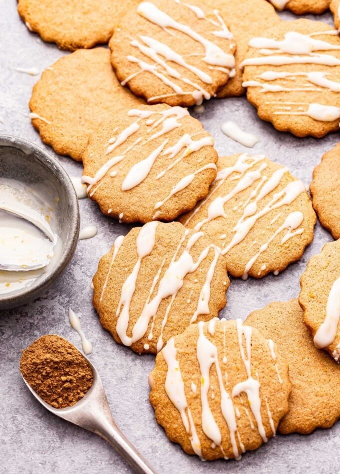 Chai Ginger Cookies drizzled with glaze and scattered on a countertop.