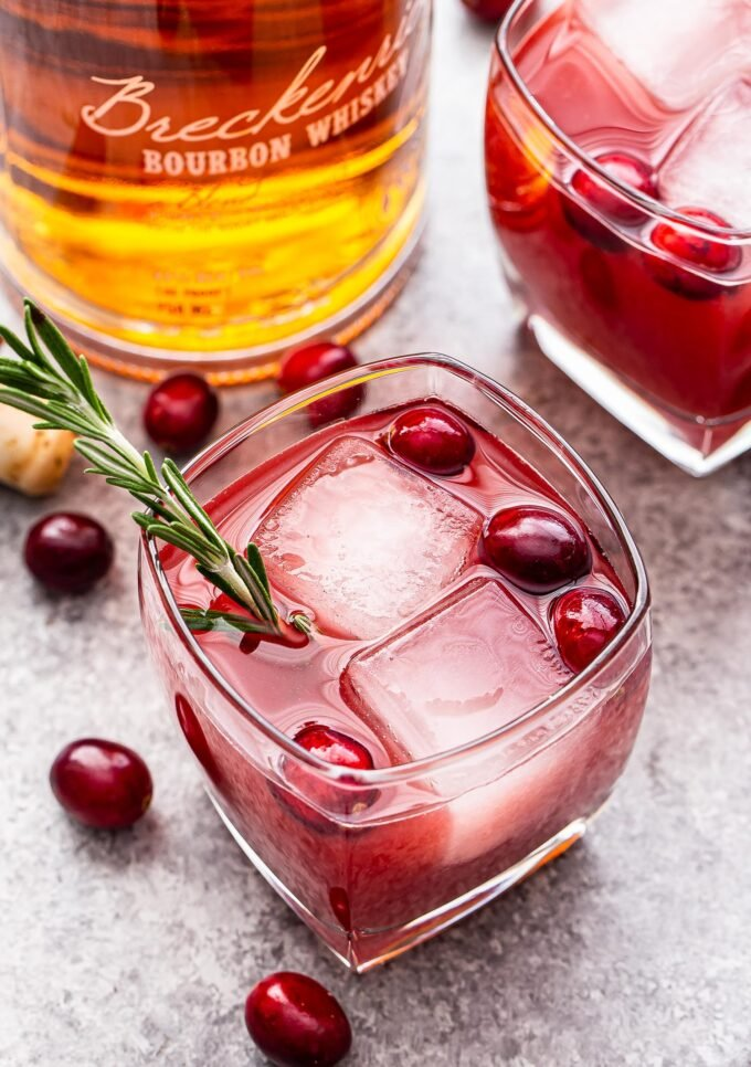 Cranberry Orange Bourbon Cocktail in a lowball glass topped with fresh cranberries and a sprig of rosemary. A second cocktail and a bottle of bourbon are in the background.