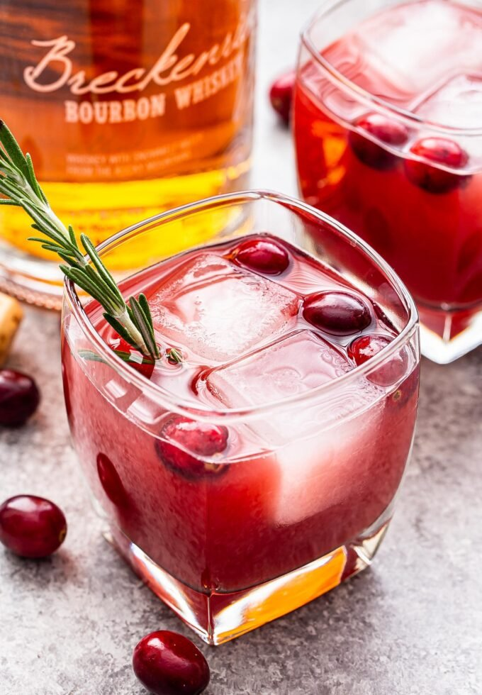 Cranberry Orange Bourbon Cocktail in a lowball glass topped with fresh cranberries and a sprig of rosemary.