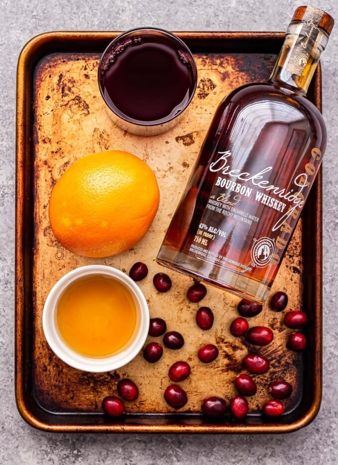 Ingredients used to make Cranberry Orange Bourbon Cocktail on a sheet pan.