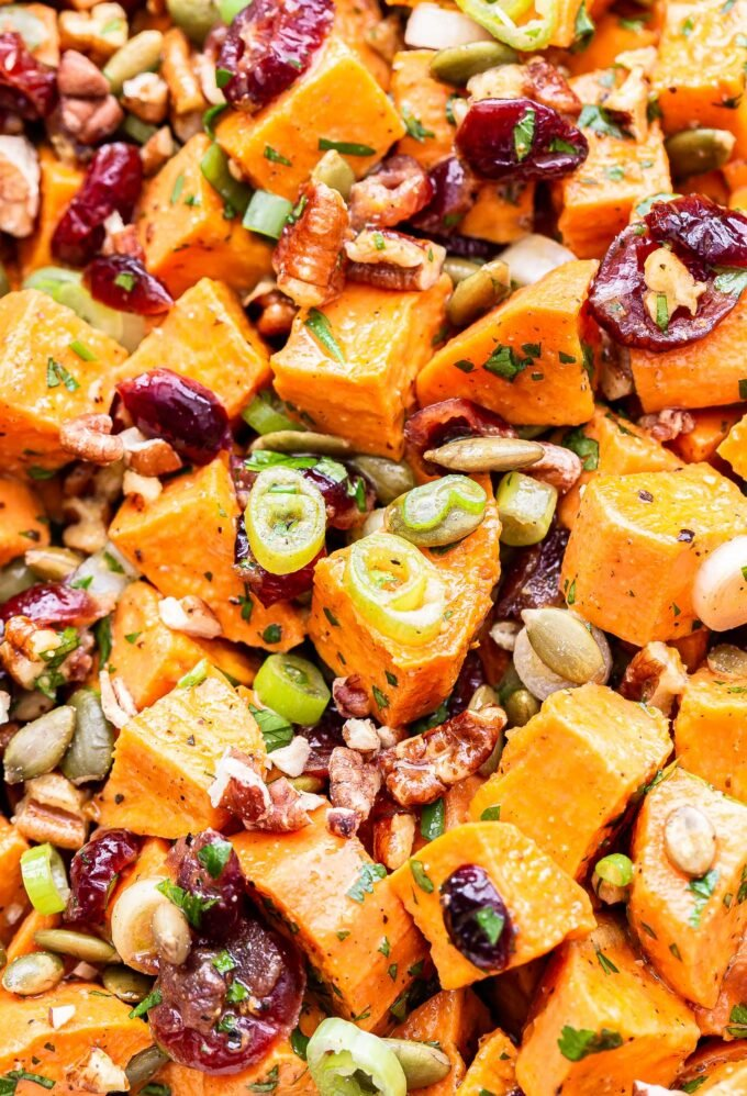 closeup photo of Maple Orange Sweet Potato Salad with pecans, green onions, dried cranberries and pepitas.