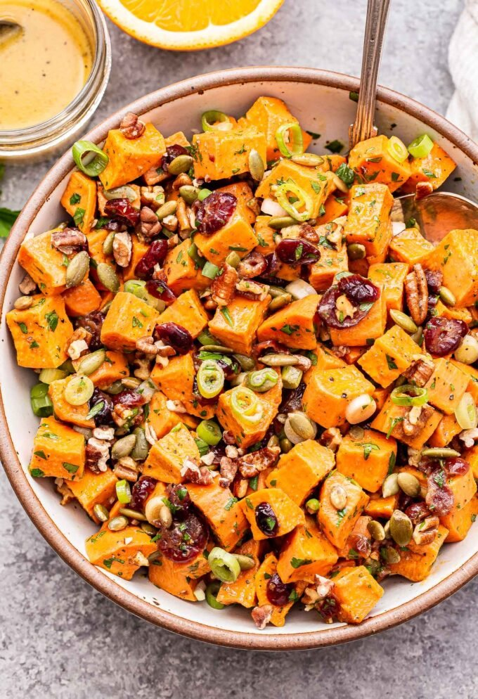 Maple Orange Sweet Potato Salad in a white serving bowl with spoons. A jar of the vinaigrette behind the bowl.