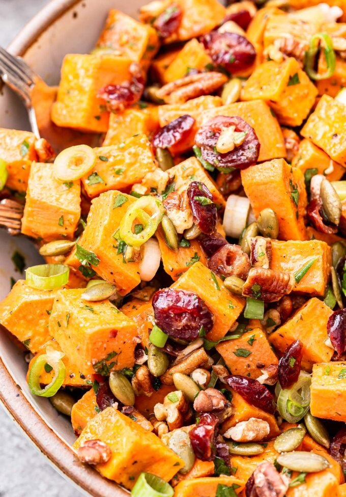 Maple Orange Sweet Potato Salad in a white bowl with cranberries, pecans, green onions and pepitas.