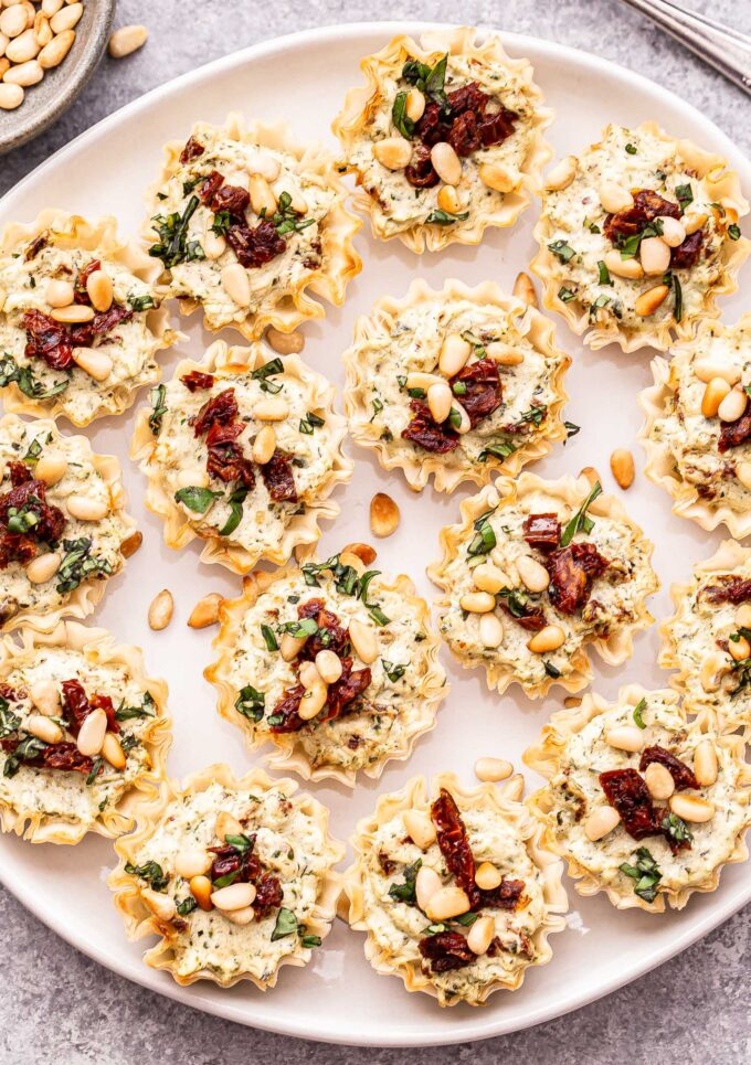 Sun Dried Tomato Pesto Goat Cheese Bites on a white plate topped with pine nuts and basil.