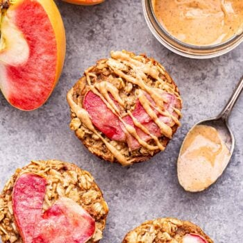 Three Apple Cinnamon Baked Oatmeal Cups with a jar of almond butter and spoon next to them.