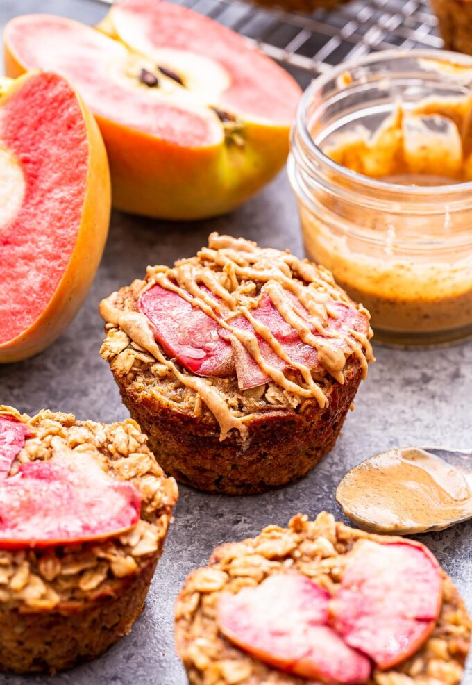 Apple Cinnamon Baked Oatmeal Cups drizzled with almond butter and a sliced apple behind them.