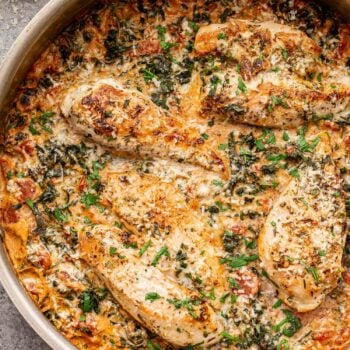 Creamy Italian Chicken in a metal skillet. Topped with parmesan cheese and basil.