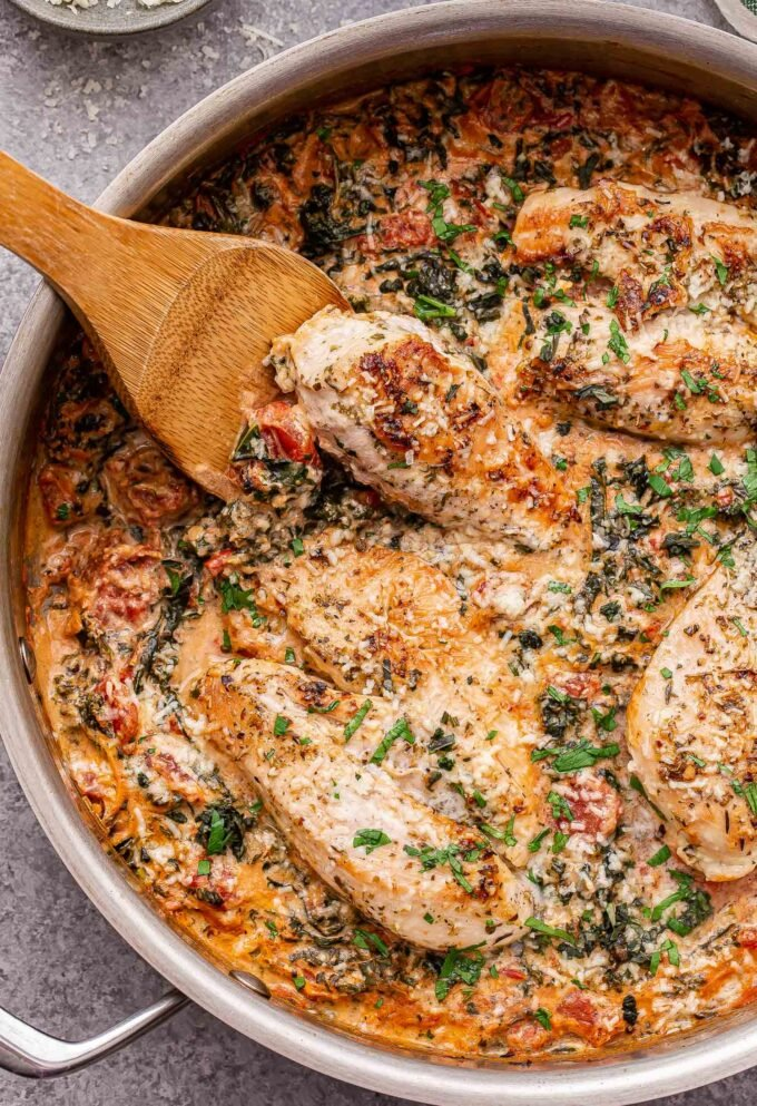 Creamy Italian Chicken in a skillet with a wooden spoon in the skillet.