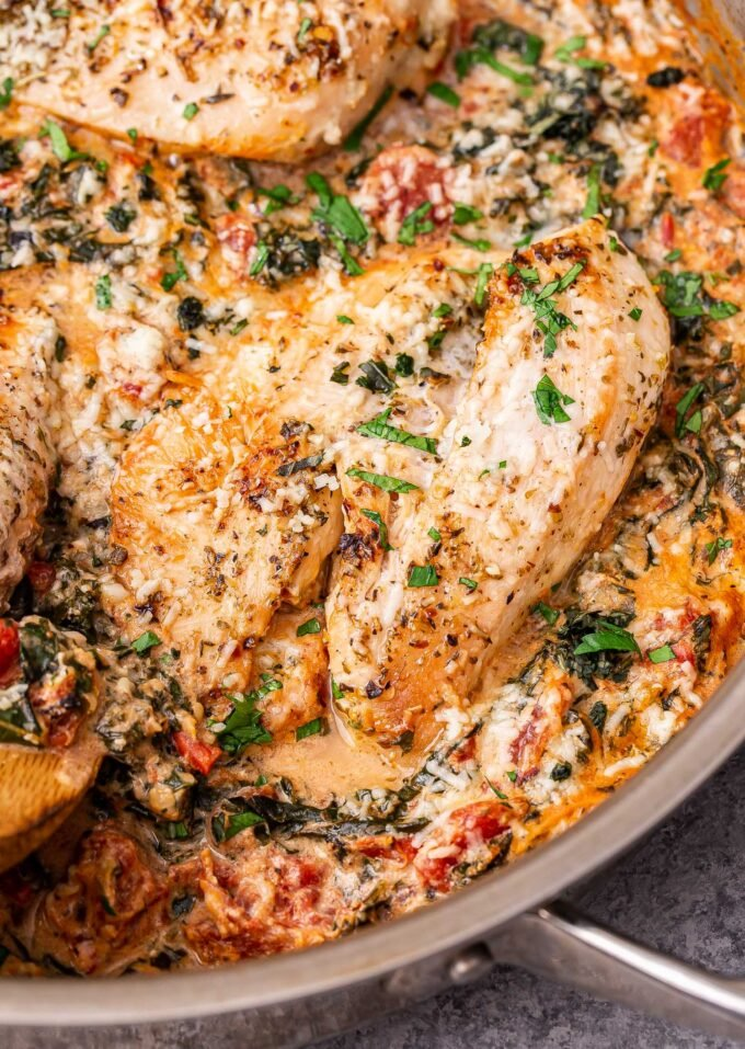 Creamy Italian Chicken in a metal skillet topped with chopped basil.