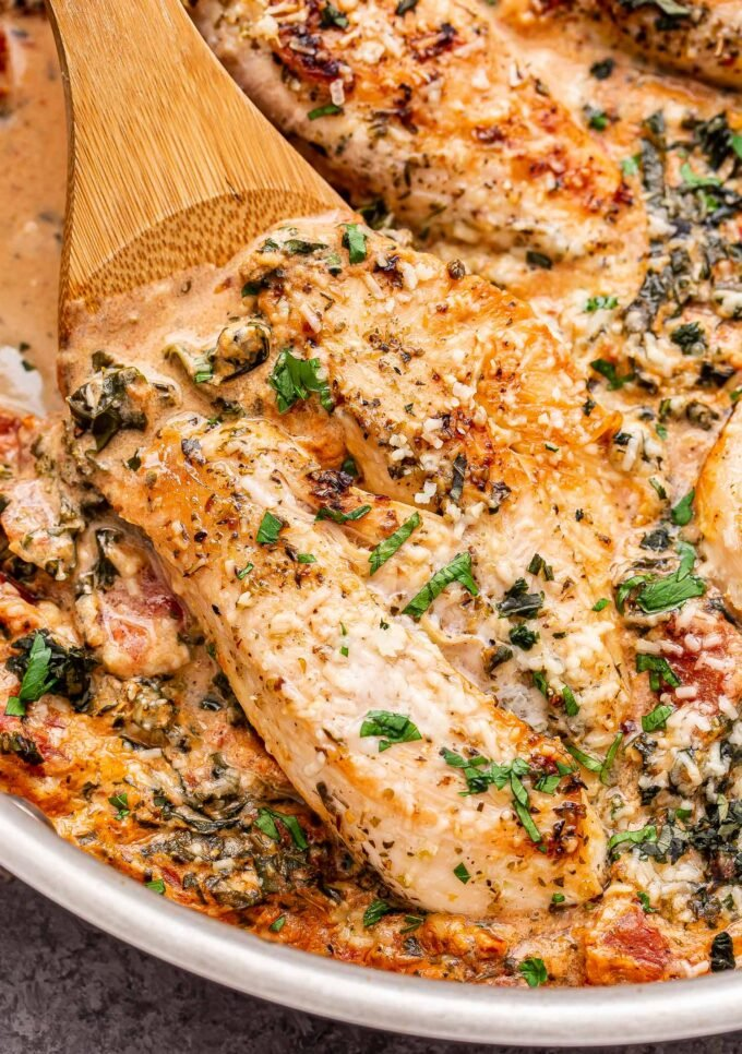 Wooden spoon hold one of the chicken breasts in the Creamy Italian Chicken Skillet.