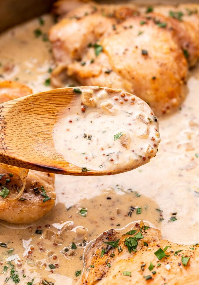 wooden spoon holding up creamy mustard sauce.