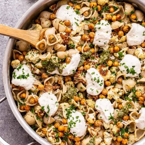 Skillet filled with Roasted Cauliflower and Chickpea Pesto Pasta with a wooden serving spoon in the skillet.
