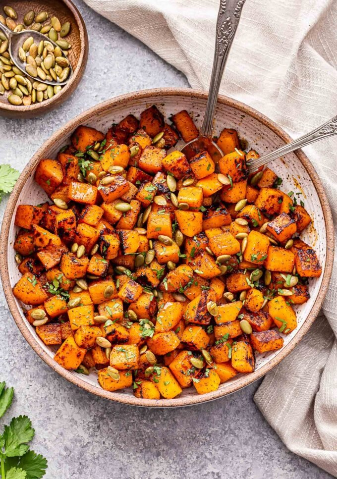 Sweet and Spicy Roasted Butternut Squash in a white bowl with spoons. A bowl of pepitas behind it.