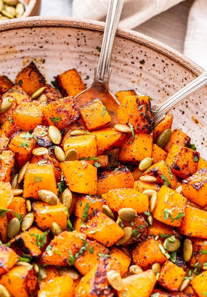 Sweet and Spicy Roasted Butternut Squash with pepitas in a white serving bowl.
