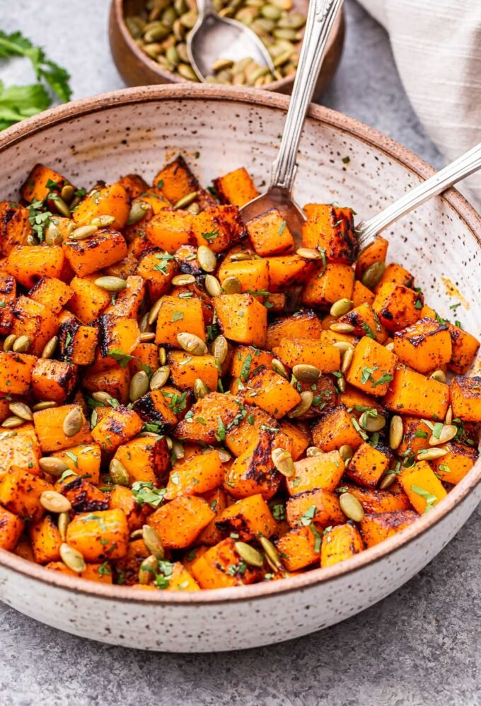 Sweet and Spicy Roasted Butternut Squash in a white bowl with spoons in it.
