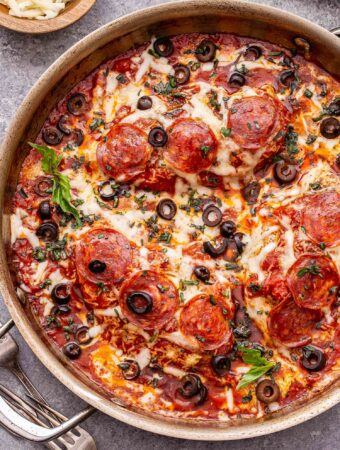 Baked pizza chicken topped with melted cheese, pepperoni and black olives in a metal skillet.