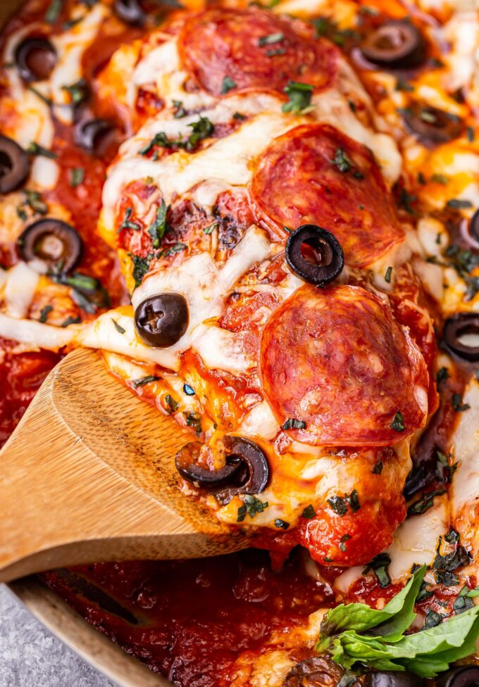 Wooden spoon holding up a Baked Pizza Chicken breast covered in melted cheese and topped with pepperoni and black olives.