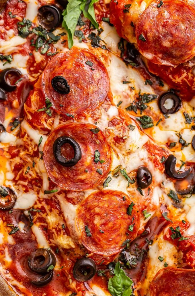 baked pizza chicken breast topped with melted cheese, pepperoni, black olives and chopped basil.