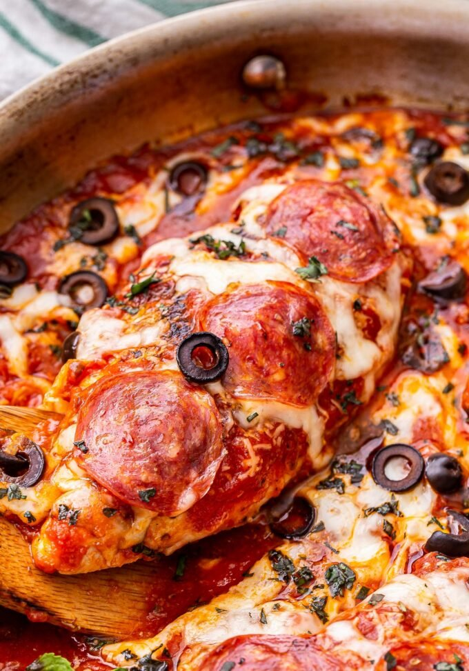 Closeup of a Baked Pizza Chicken breast covered in melted cheese and topped with pepperoni and black olives.