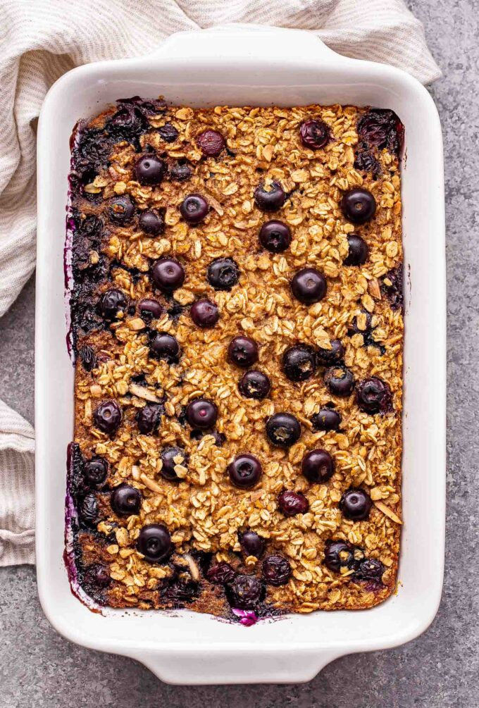 Blueberry Maple Baked Oatmeal in a white baking dish with a white dish towel under it.