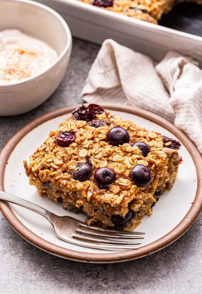 A slice of Blueberry Maple Baked Oatmeal on a white plate with a fork and a bowl of greek yogurt behind it.