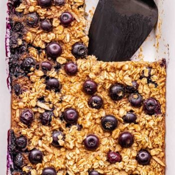 Blueberry Maple Baked Oatmeal in a white baking dish with a corner piece cut out and a black spatula in it's place.