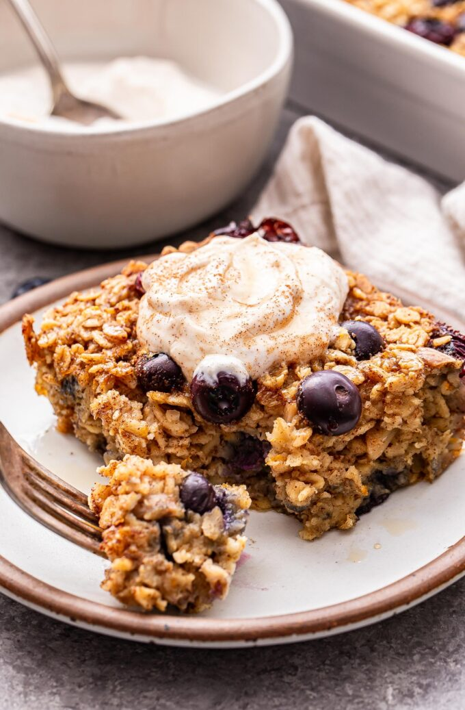 A slice of Blueberry Maple Baked Oatmeal on a white plate with a fork holding a bite sized piece.