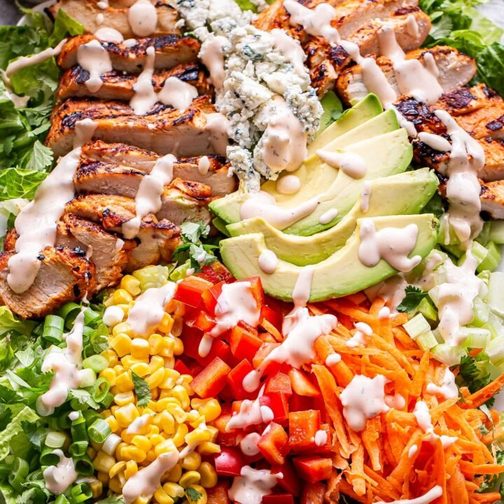 buffalo chicken salad drizzled with spicy ranch dressing on a white serving platter.