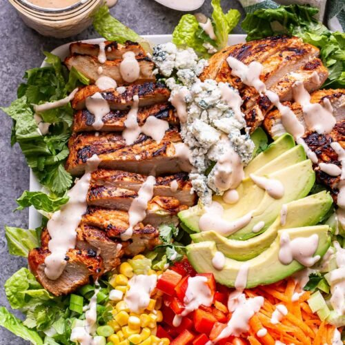 buffalo chicken salad topped with avocado, peppers, carrots, corn and spicy ranch dressing on a white plate with a jar of dressing and a spoon behind it.