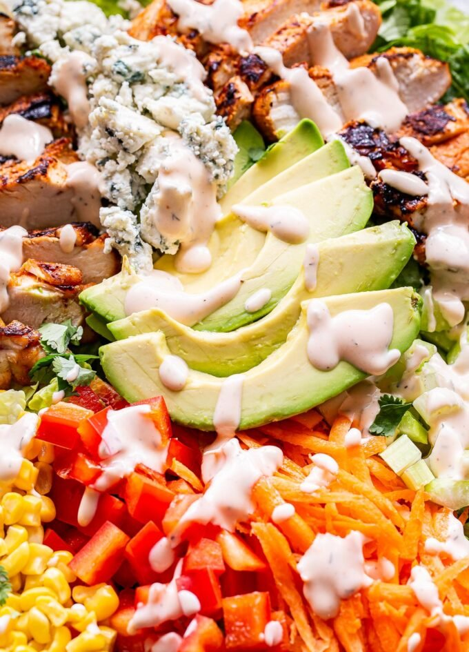 buffalo chicken salad topped with avocado, peppers, carrots, corn and spicy ranch dressing