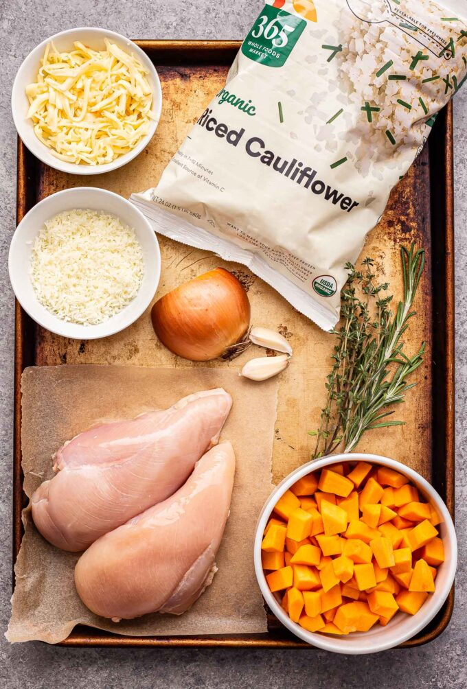 Ingredients used to make Cheesy Chicken, Butternut Squash and Cauliflower Rice Skillet on a sheet pan.