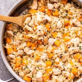 Cheesy Chicken, Butternut Squash and Cauliflower Rice in a metal skillet with a wooden spoon in the skillet.