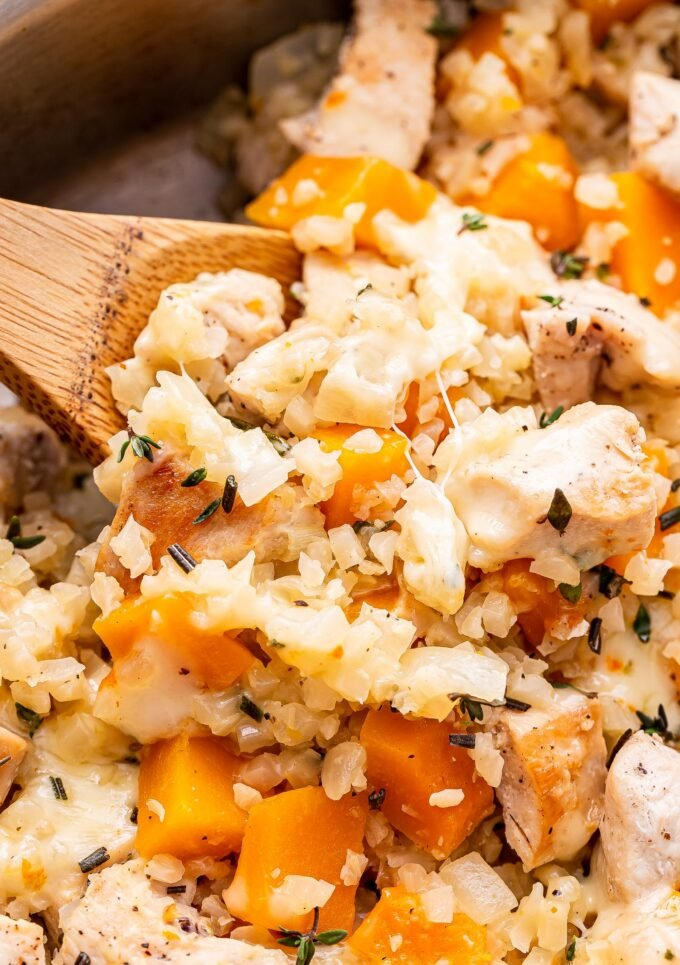 Wooden spoon holding up some of the Cheesy Chicken, Butternut Squash and Cauliflower Rice.