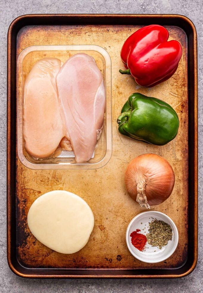 ingredients used to make the chicken cheesesteak skillet on a sheet pan.