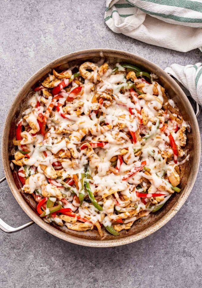 Chicken Cheesesteak Skillet with red and green peppers, onions and melted provolone cheese on top.