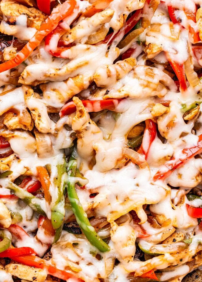 closeup of the thin slices of chicken, bell peppers, onions and melted provolone cheese.