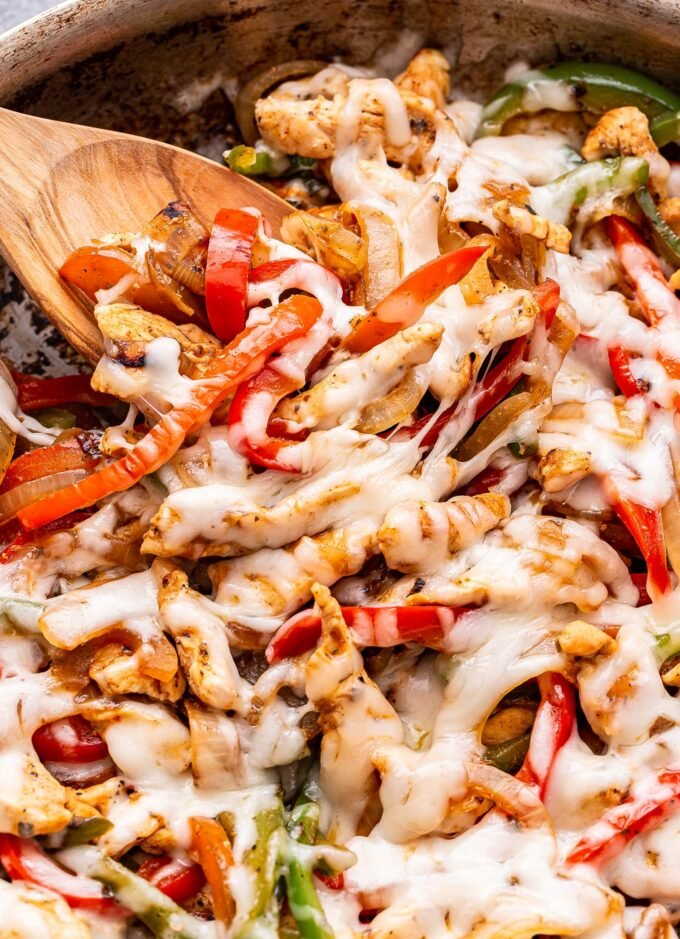 Closeup of Chicken Cheesesteak Skillet with red and green peppers, onions and melted provolone cheese on top. A wooden spoon is in the skillet.