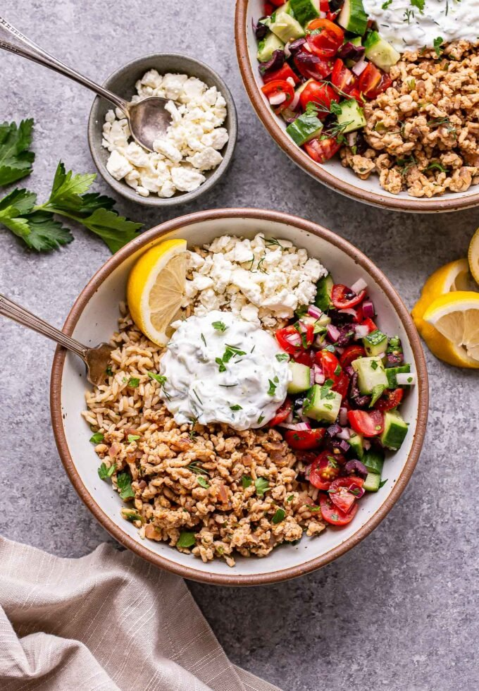 Two Greek chicken bowl with rice, tzatziki and tomato cucumber salad in them and a small bowl of feta cheese off to the side.