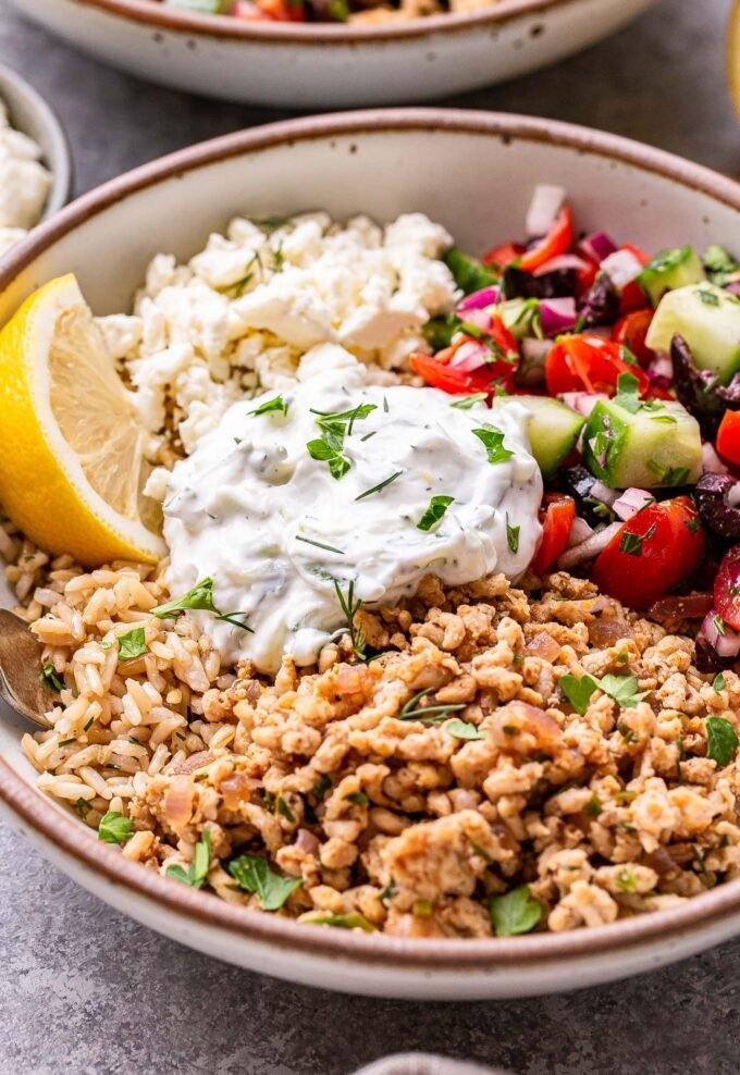 White bowl filled with rice, greek chicken, tomato cucumber salad, tzatziki and crumbled feta.