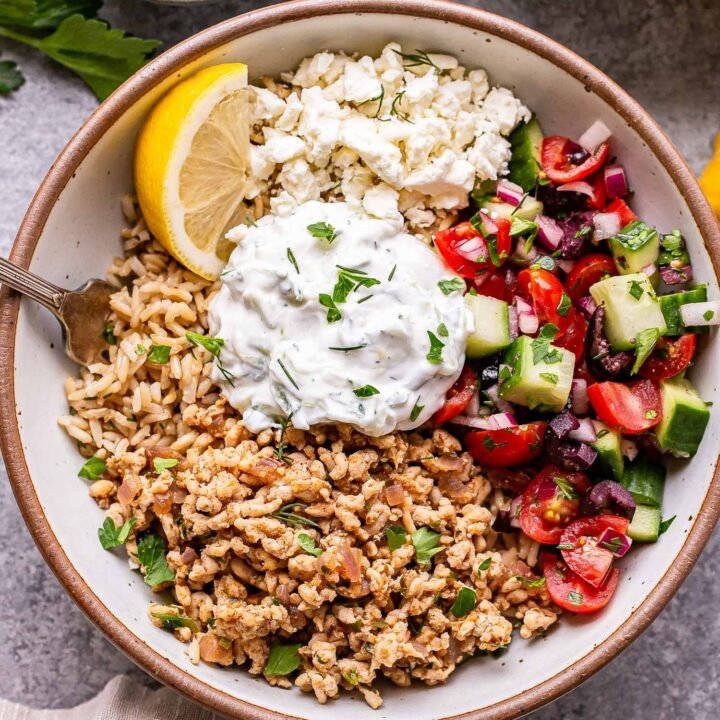 Greek chicken bowl with rice, tzatziki and tomato cucumber salad in a white bowl with a small bowl of feta cheese behind it.