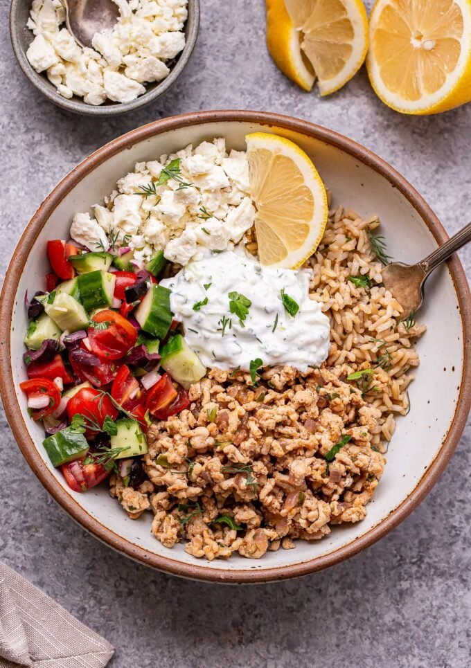Greek chicken bowl with rice, tzatziki and tomato cucumber salad in a white bowl with a small bowl of feta cheese and lemon wedges behind it.