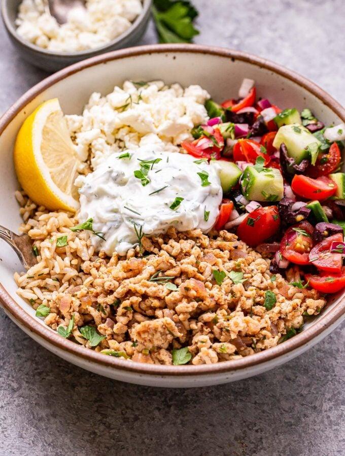 Greek Chicken Bowls with ground chicken, rice, tzatziki, feta and greek salad.
