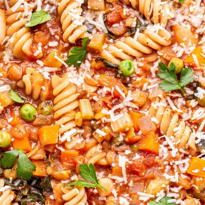Lentil Minestrone Soup with rotini pasta in a white bowl topped with parmesan cheese and parsley.