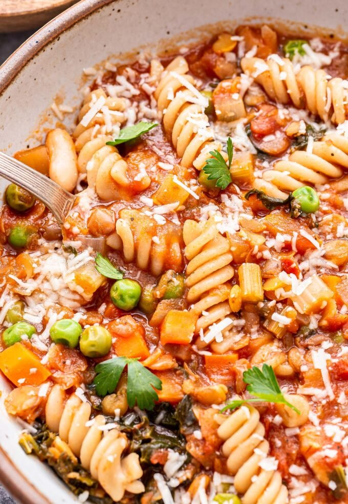 Lentil Minestrone Soup with rotini pasta in a white bowl with a spoon.